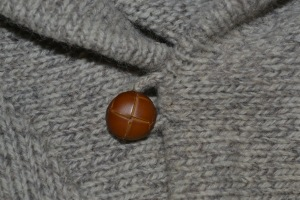 Close up of vintage shawl collar button closure.
